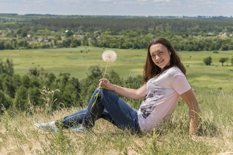 Woman with big dandelion on sky background. Copy space. Summer concept.  stock photos