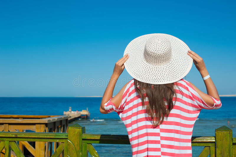 Woman in a big hat looking at the sea.  stock images