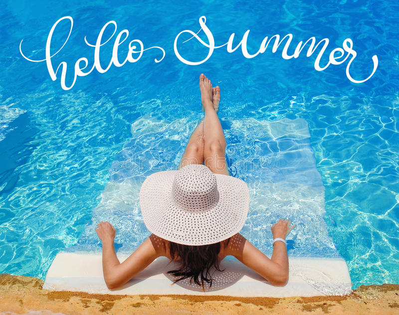 Woman in big hat lying on lounger by the pool and text Hello Summer, Calligraphy lettering stock photo