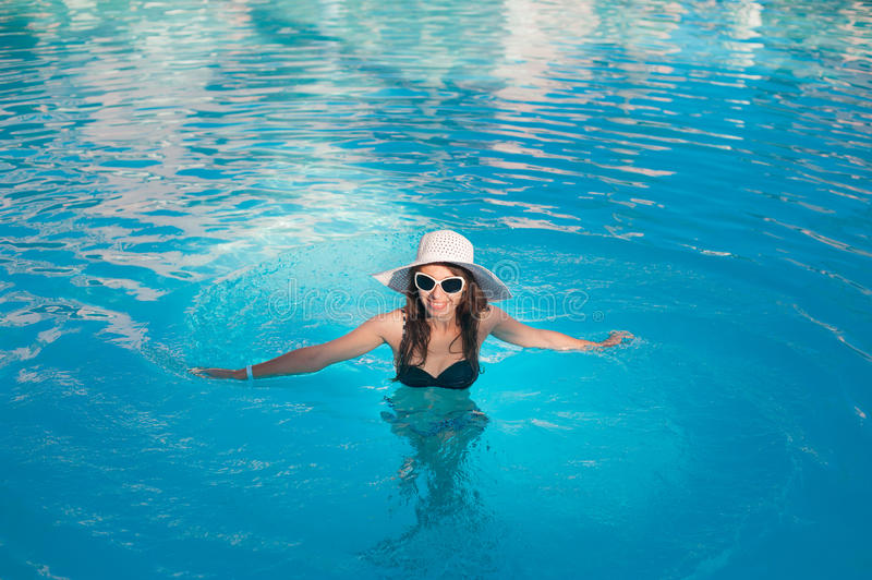 Woman in big hat relaxing on the swimming pool.  stock photography