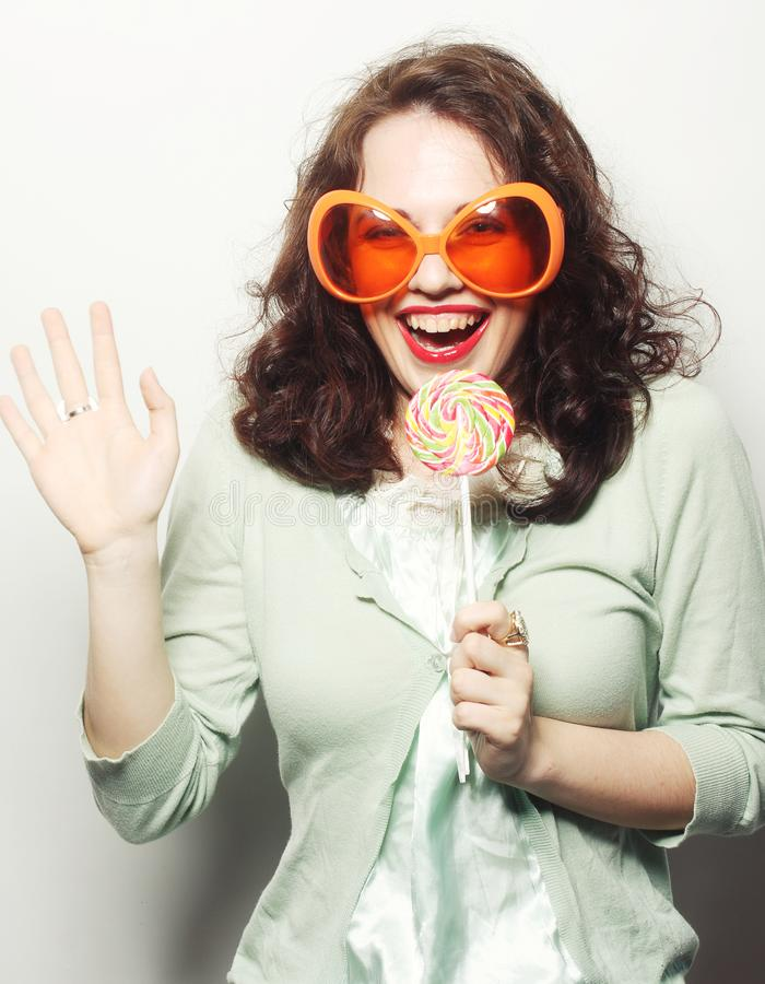 Woman in big orange glasses licking lollipop with her tongue. Young funny woman in big orange glasses licking lollipop with her tongue stock photography