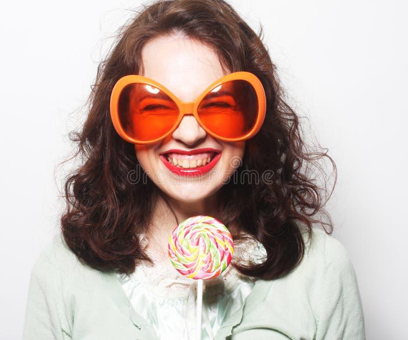Woman in big orange glasses licking lollipop with her tongue. Young funny woman in big orange glasses licking lollipop with her tongue stock photo