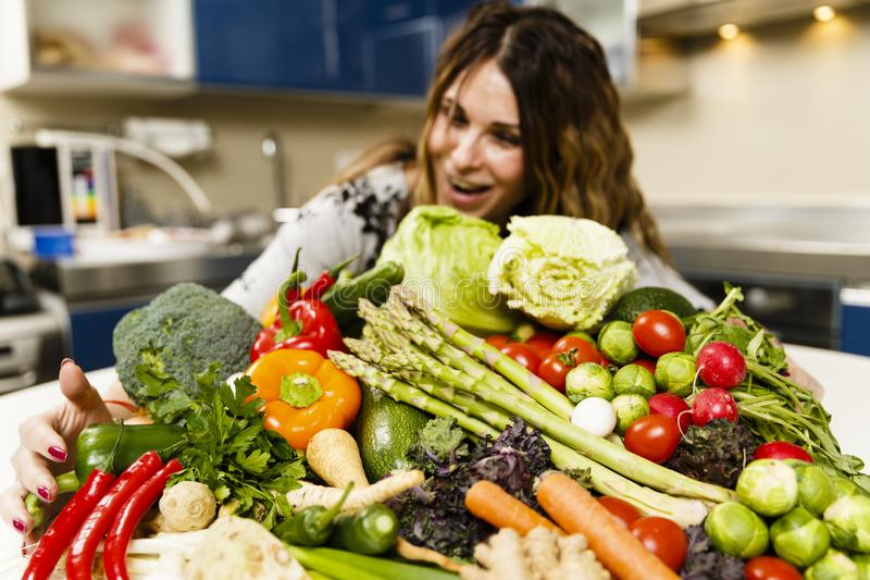 Woman with a big pile of vegetables. In the kitchen royalty free stock photography