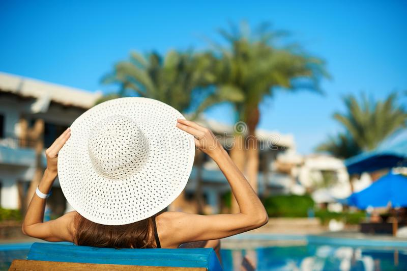 Woman in big white hat lying on a lounger near the swimming pool at the hotel, concept summer time to travel royalty free stock images