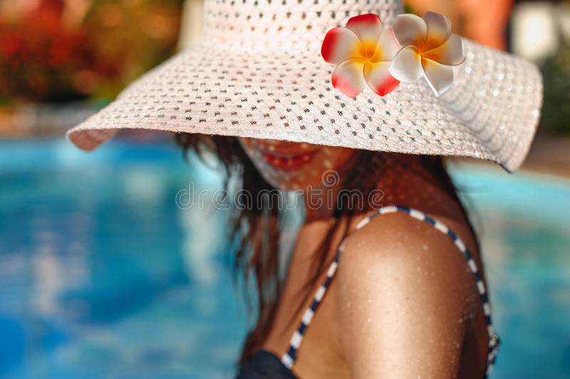 Woman in a big white hat posing near pool royalty free stock photos