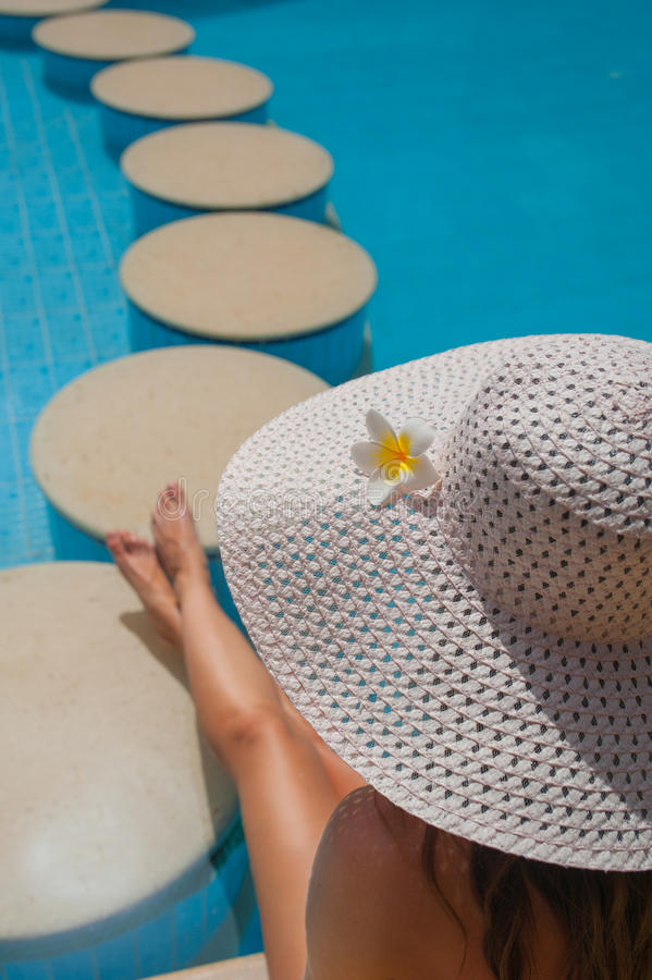 Woman in a big white hat sits on the edge of the pool with stones.  royalty free stock photos