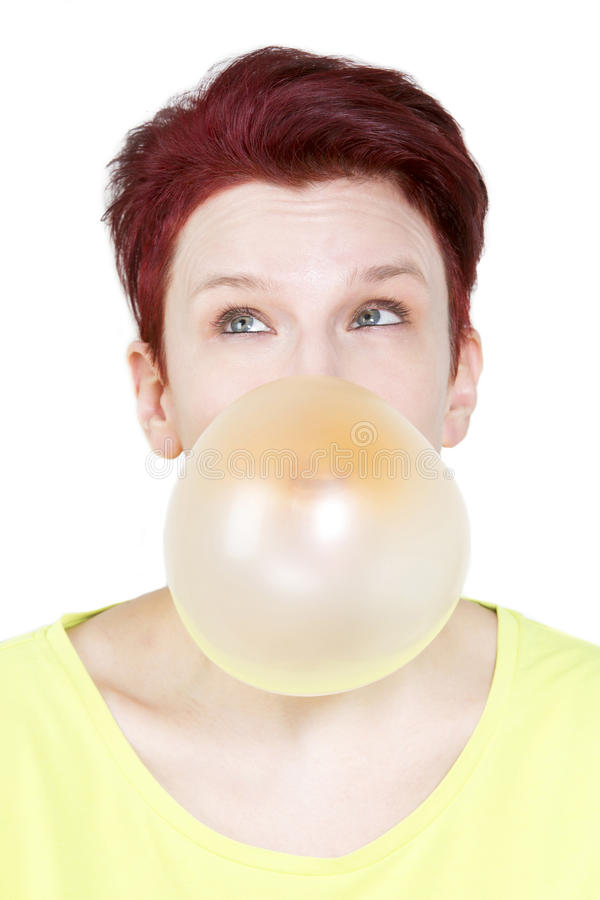 Woman with big yellow bubble of chewing gum. Red-haired woman blowing a big bubble of chewing gum royalty free stock images