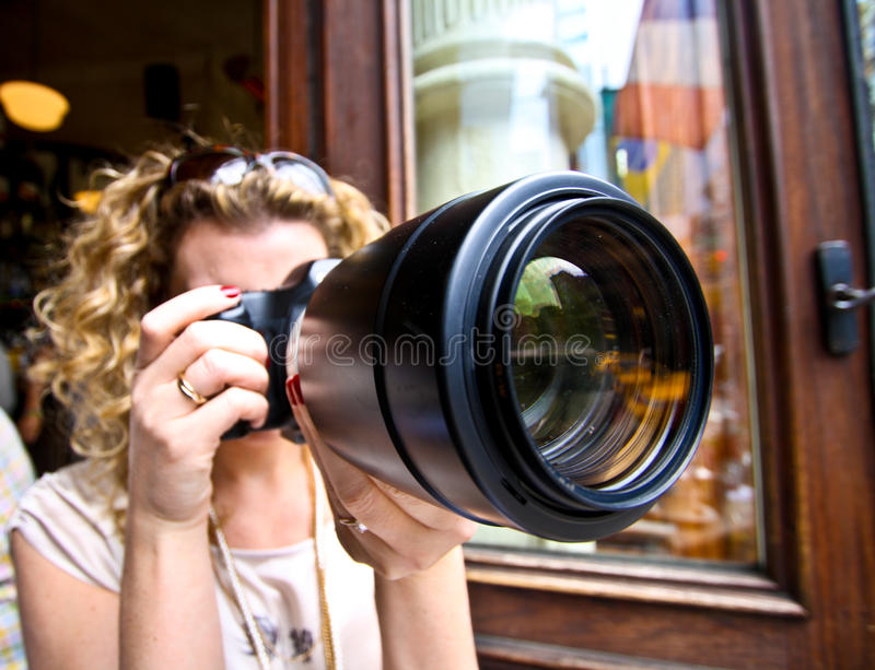 Woman with a big zoom. Woman Shooting with a huge tele zoom lense (70 200 2.8 shot with a wide angle lense stock images