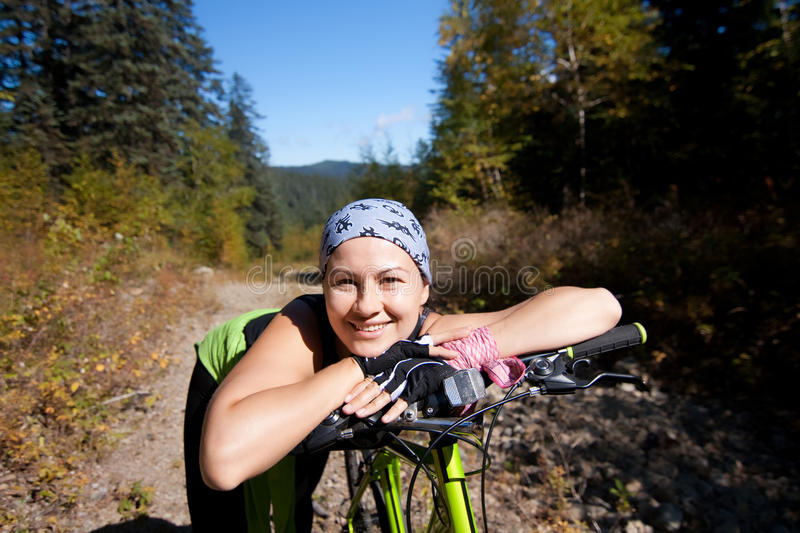 Woman on bike. Young woman on a bike in mountains royalty free stock images