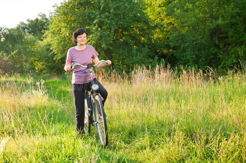 Woman on a bike on the background of nature royalty free stock photos