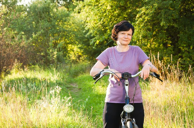 Woman on a bike on the background of nature royalty free stock photo