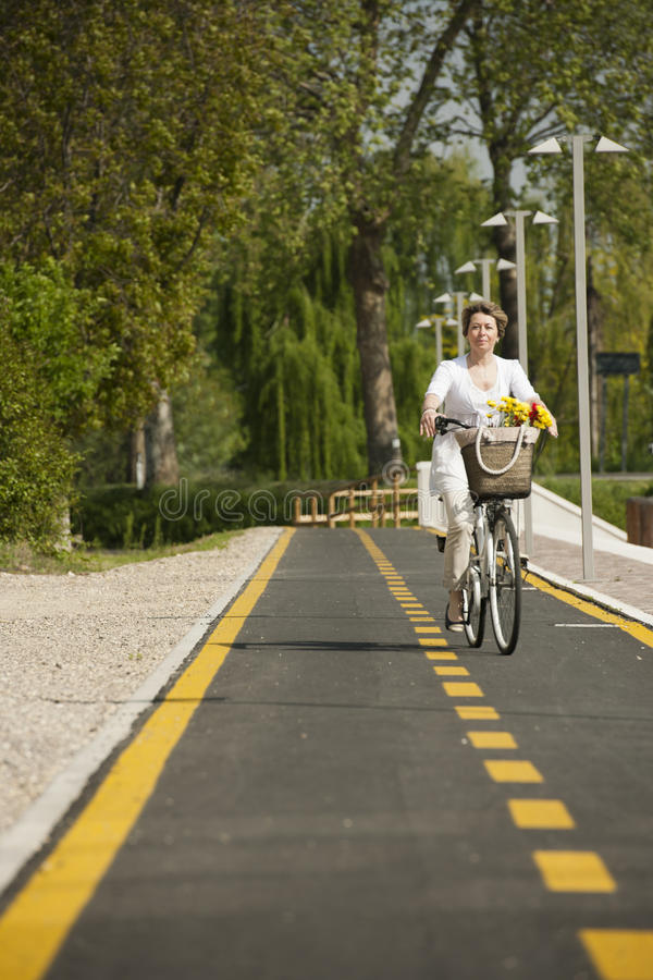 Woman With Bike On The Bikeway Stock Images
