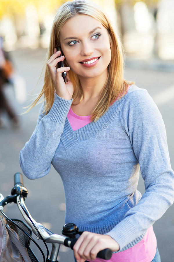 Download Woman On Bike With Mobile Phone Royalty Free Stock Photos - Image: 27708368