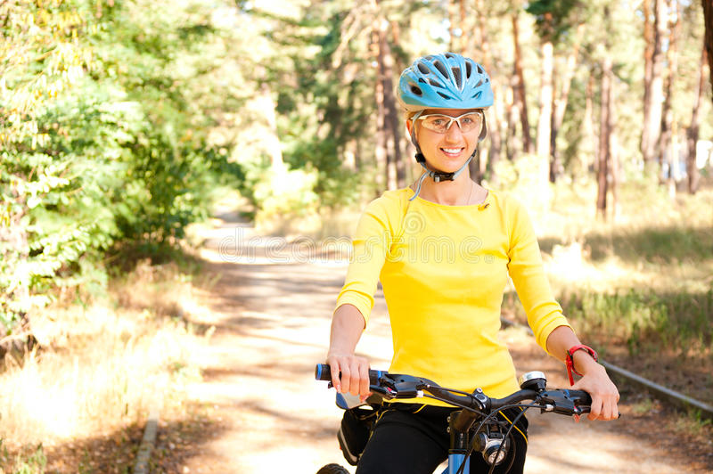 Woman on the bike in the sunny royalty free stock image