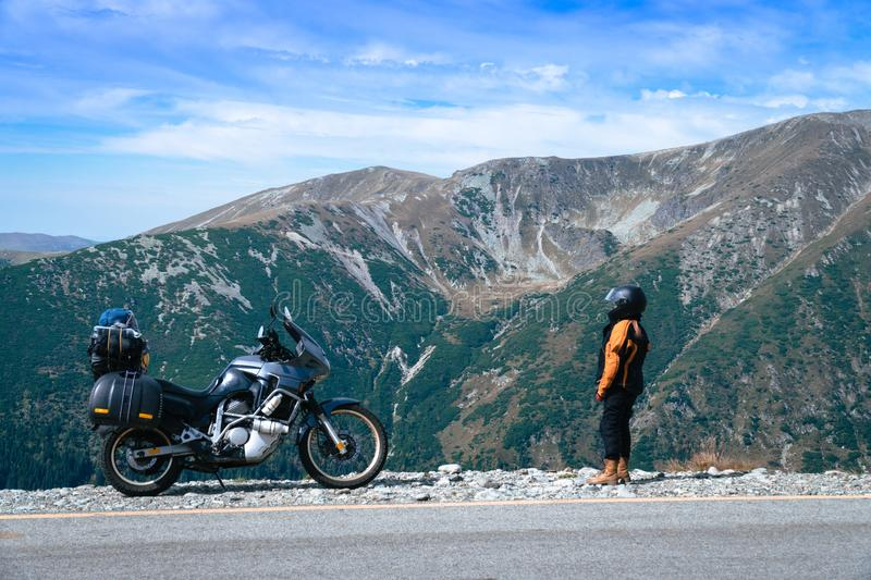 Woman biker and adveture motorcycle top mountain road. Travel, vacation in Europe, motorcyclist way, tourism, Transalpina, Romania royalty free stock photography