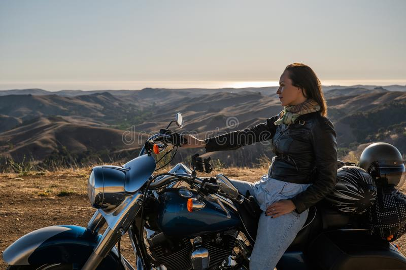 Woman biker sitting on her motorcycle stock images