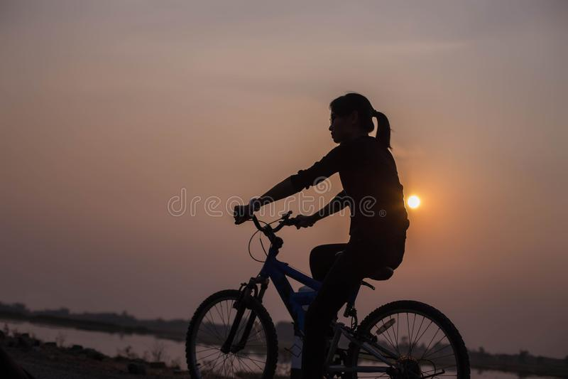 Woman biking hands at sunset royalty free stock photo