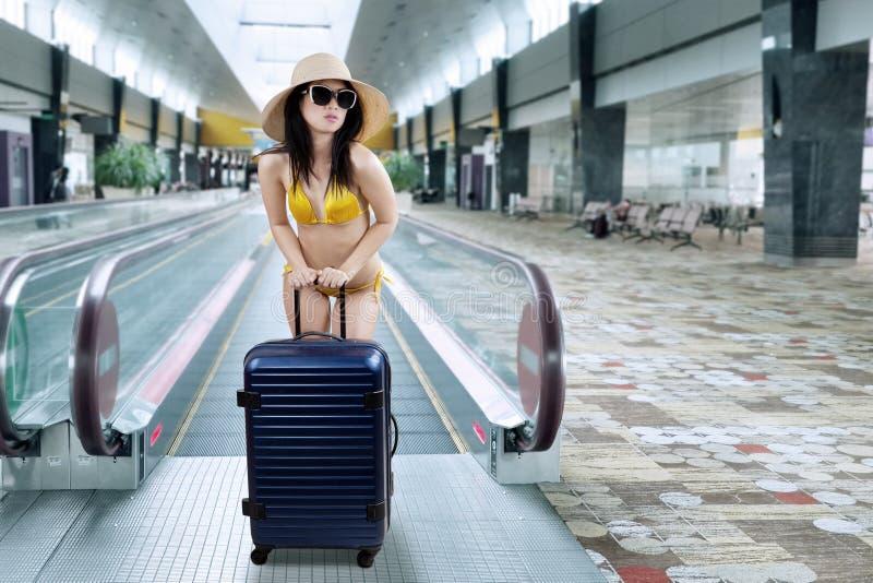 Woman with bikini in airport corridor stock photo