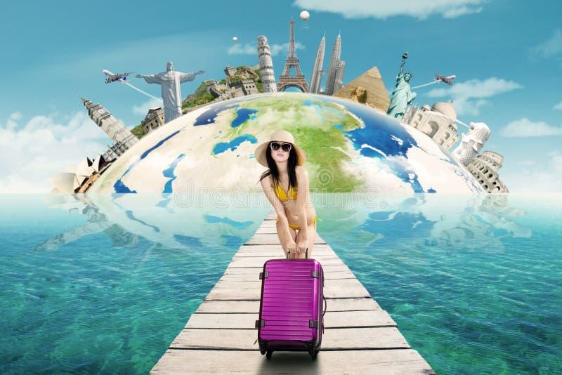 Woman with bikini and bag to travel the worldwide stock photography