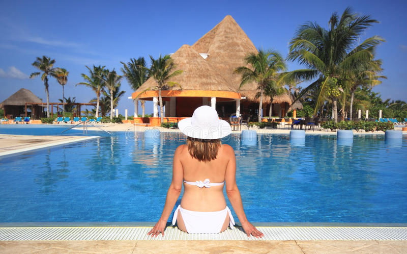 Woman in a bikini by beach resort swimming pool stock images