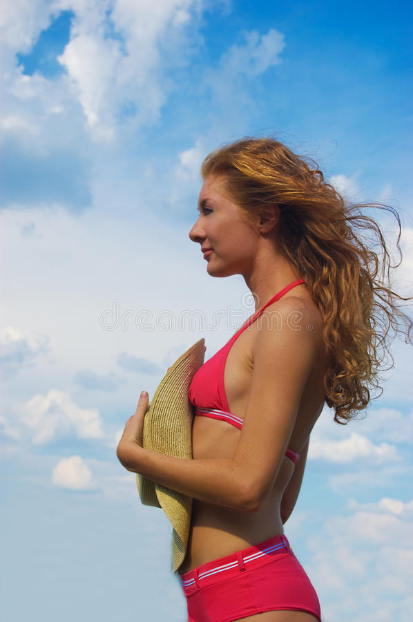 Woman in bikini with flying hair. Over dramatic sky stock photography