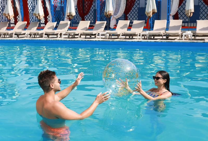 Woman in bikini and her boyfriend playing with inflatable ball at resort royalty free stock photography