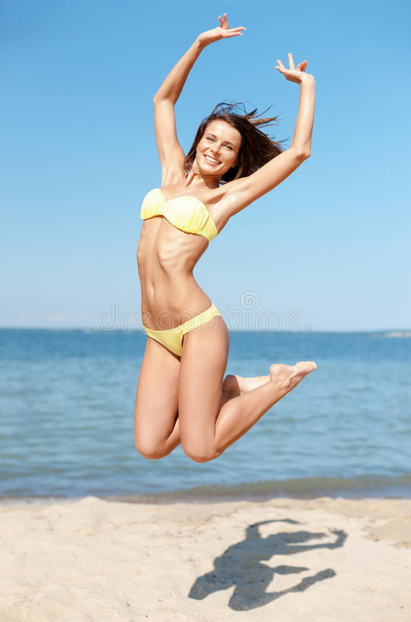 Woman in bikini jumping on the beach stock images