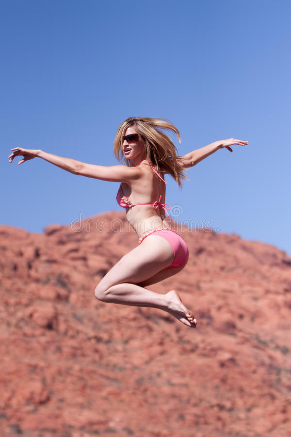 Woman in bikini jumping outdoors royalty free stock photos