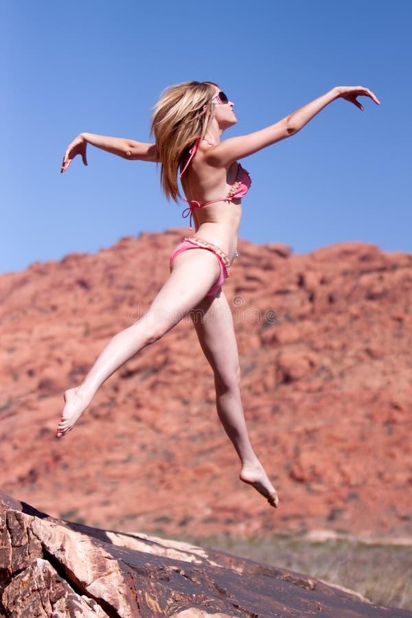 Woman in bikini jumping outdoors stock images