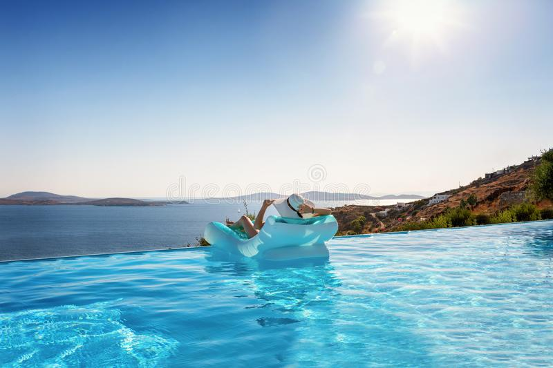 Woman relaxes on a float under the Mediterranean sun. Woman in bikini relaxes on a float over blue pool water under the Mediterranean sun and enjoys her summer stock image