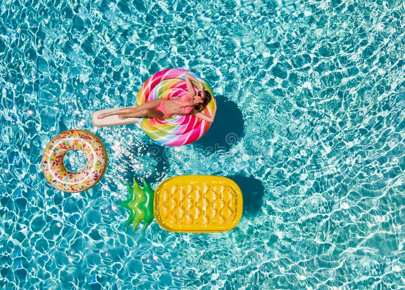 Woman in bikini relaxes on a lolli pop shaped swimming pool float. Beautiful, sportive woman in bikini relaxes on a lolli pop shaped swimming pool float during a royalty free stock photo