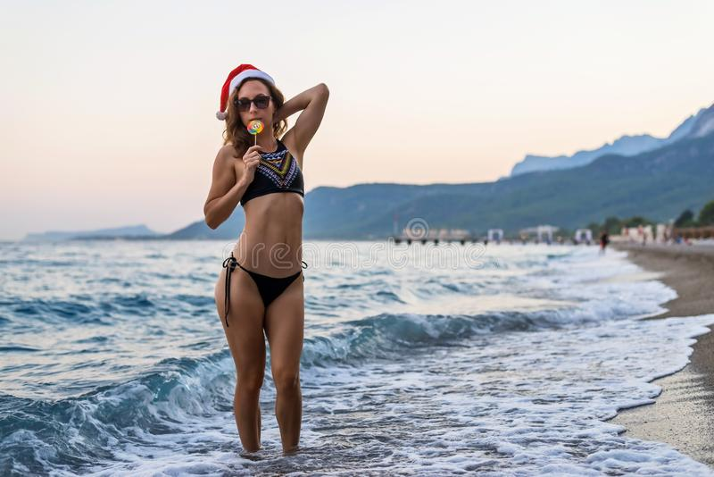 Woman in bikini and santa hat on the beach, free space. Christmas holidays. In a tropical country stock image