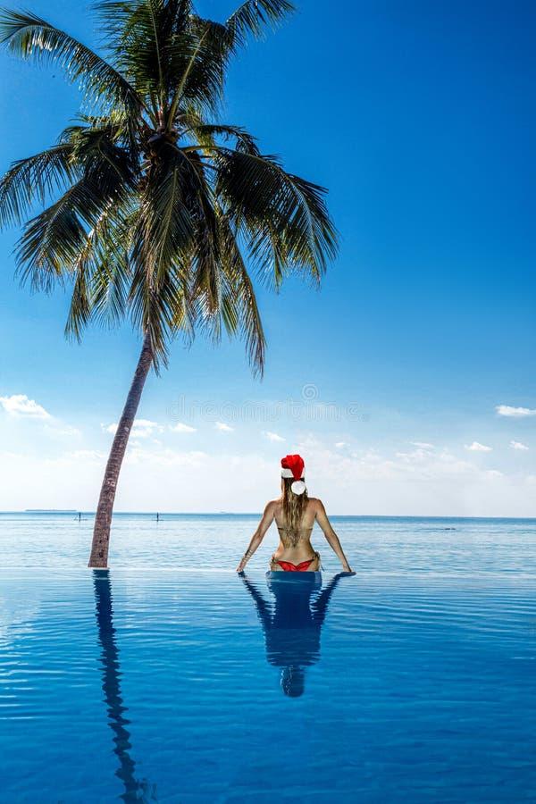 Woman in bikini and Santa hat sitting on paradise beach, enjoying winter holidays and celebrating Christmas at tropical stock image