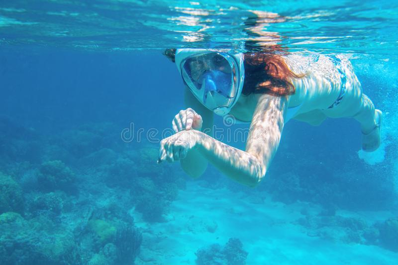 Woman in bikini show time underwater. Snorkeling in tropical sea coral reef. Young girl in full-face snorkeling mask stock images