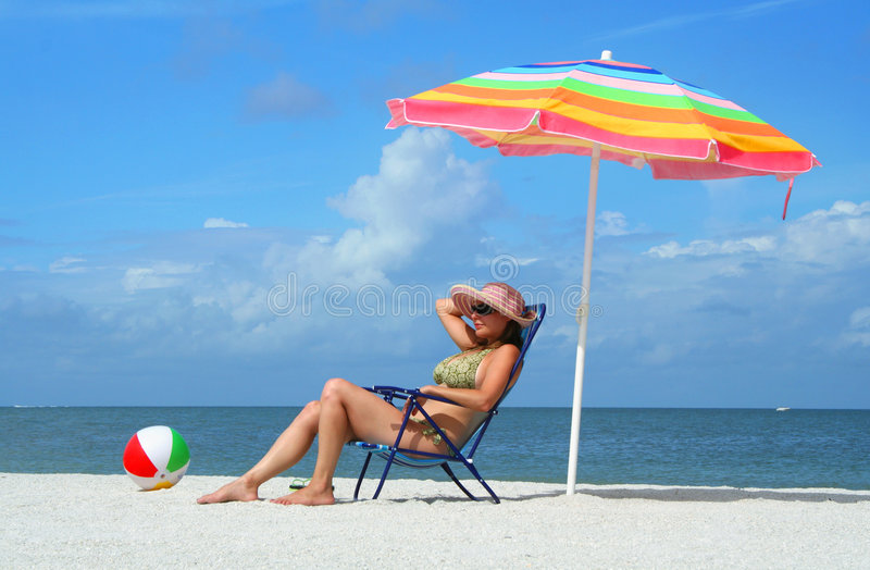 Woman in bikini tanning on the beach stock photos
