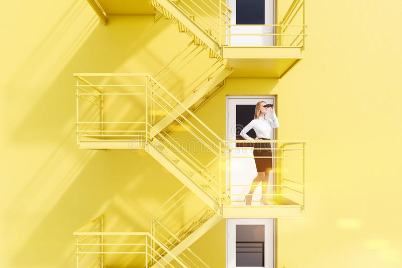 Woman with binoculars on fire exit stairs, yellow royalty free stock photography