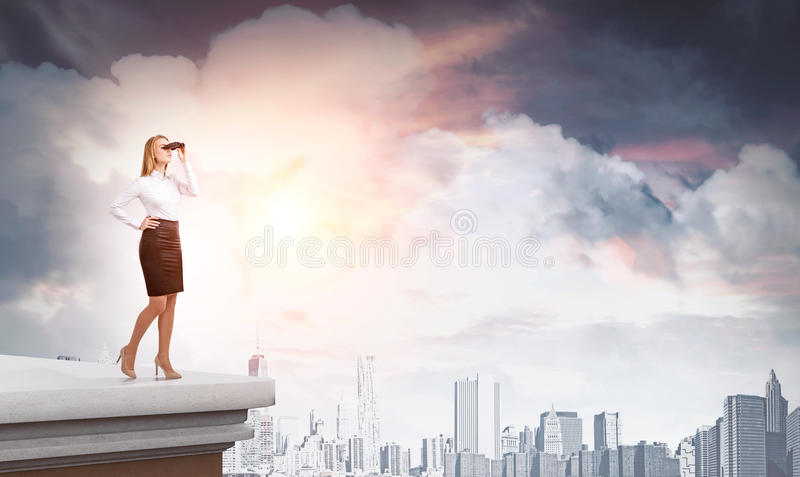 Woman with binoculars on skyscraper roof royalty free stock image