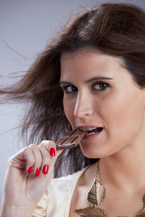 Woman biting chocolate. Young beautiful woman eating some chocolate royalty free stock photography