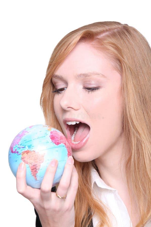 Woman biting globe. Woman biting into a globe royalty free stock photo