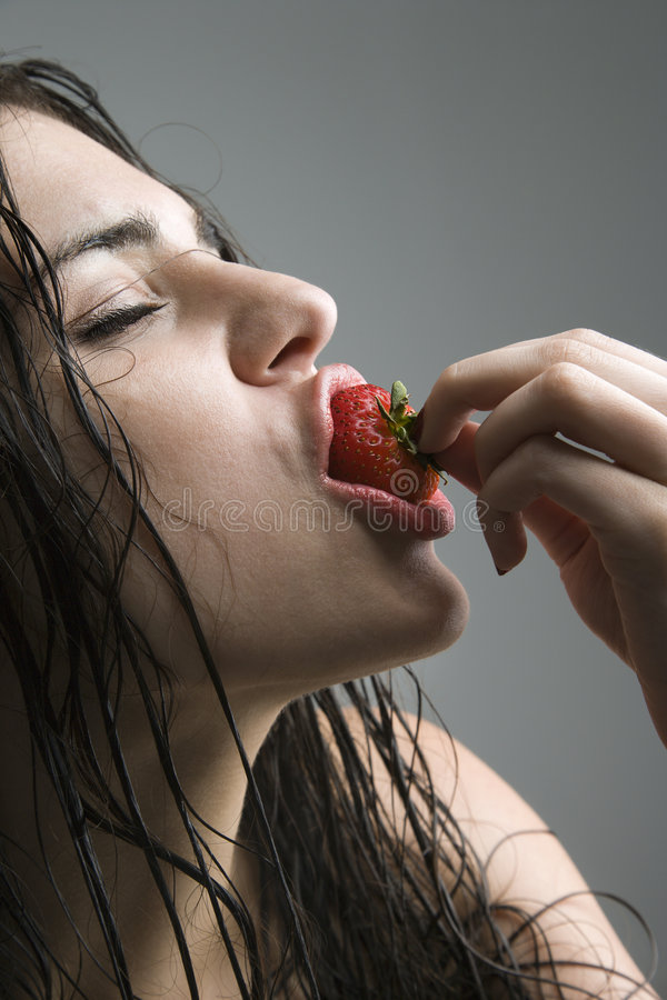 Download Woman biting strawberry. stock image. Image of eyes, closed - 2424535