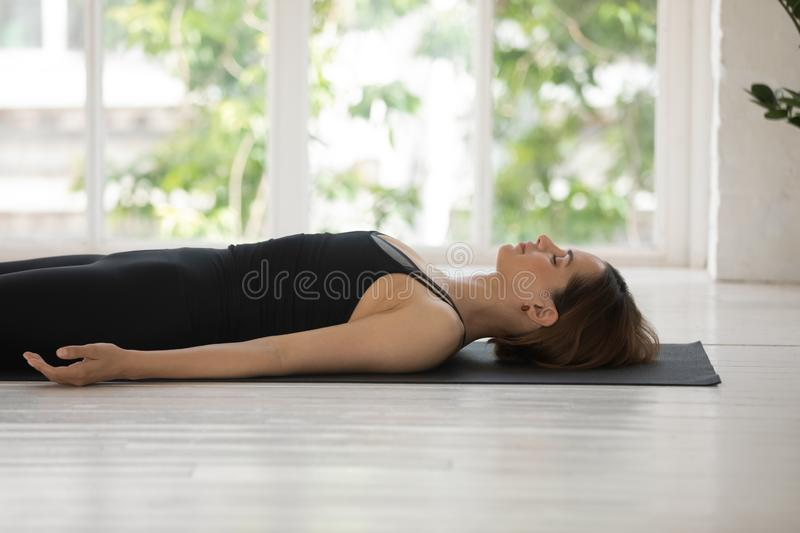Side view woman lying on mat do Corpse pose indoors royalty free stock image