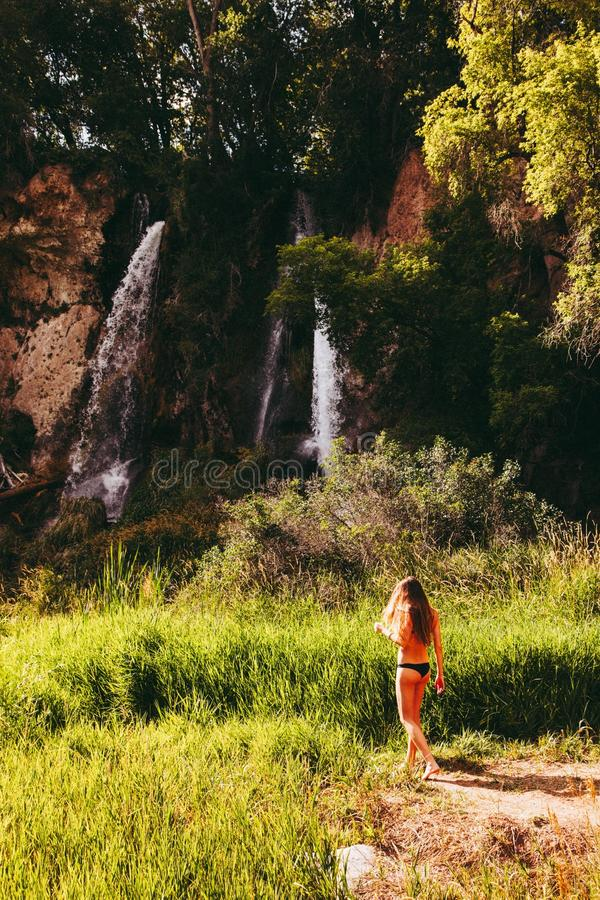 Woman In Black Bikini Bottom Walking Towards Waterfall stock photography