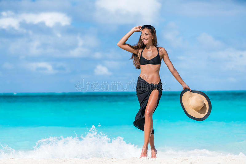Woman In Black Bikini And Sarong Walking On Beach Stock ...