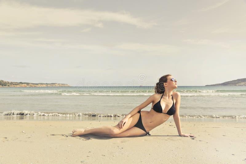 Woman in Black Bikini on Seashore royalty free stock image
