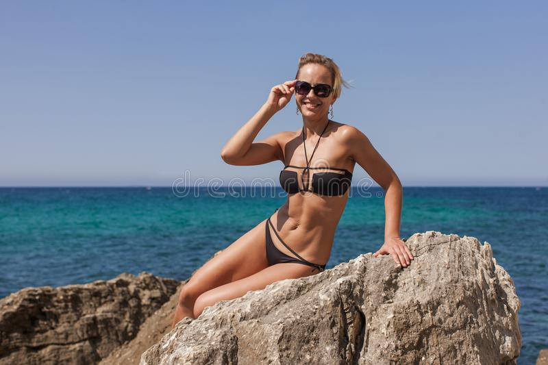 Woman in black bikini and tinted sunglasses reclining on rock royalty free stock images