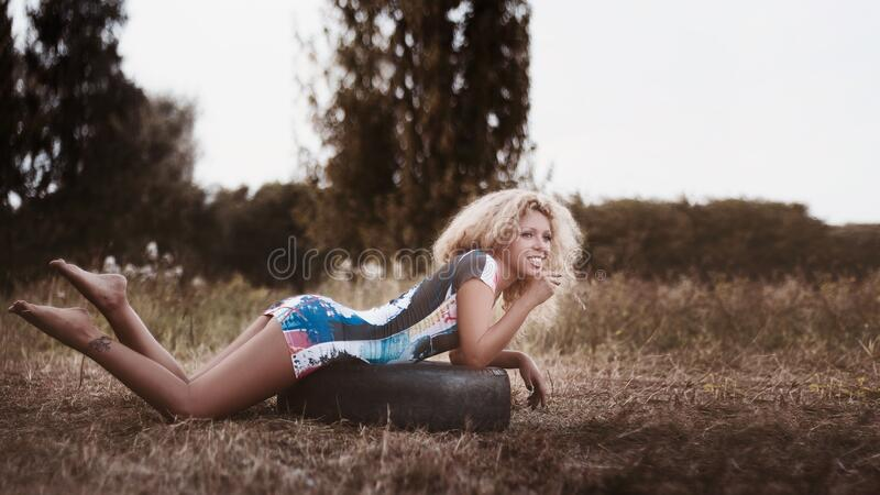 Woman In Black Blue And White Bodycon Dress Laying On Black Rubber Tire Surrounded Brown Grass Field Under Sunny Sky Free Public Domain Cc0 Image