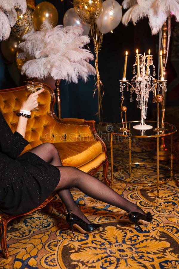 Woman in black with champagne glass at Crazy luxury corporate event decoration with feather and gold in Eastern Europe royalty free stock image