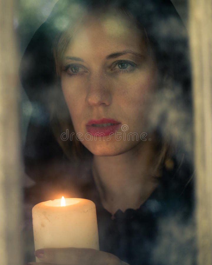 Woman in black cloak with candle royalty free stock photography