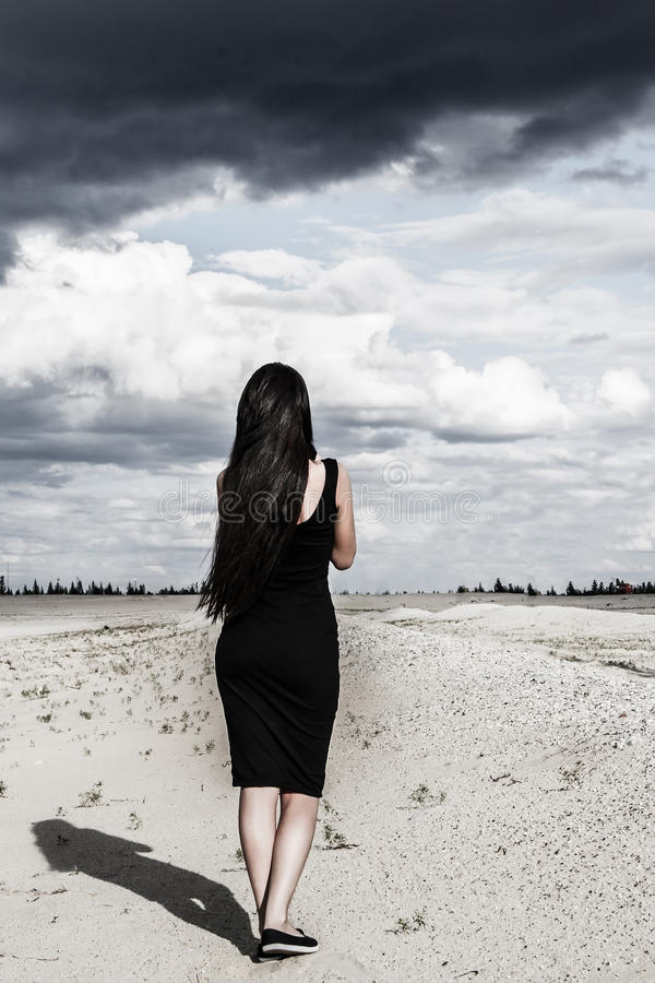 Woman in a black clothes in a desert stock image