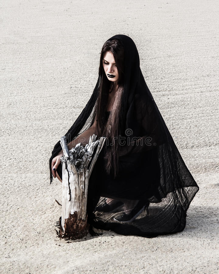 Woman in a black clothes near the dry stump stock photo